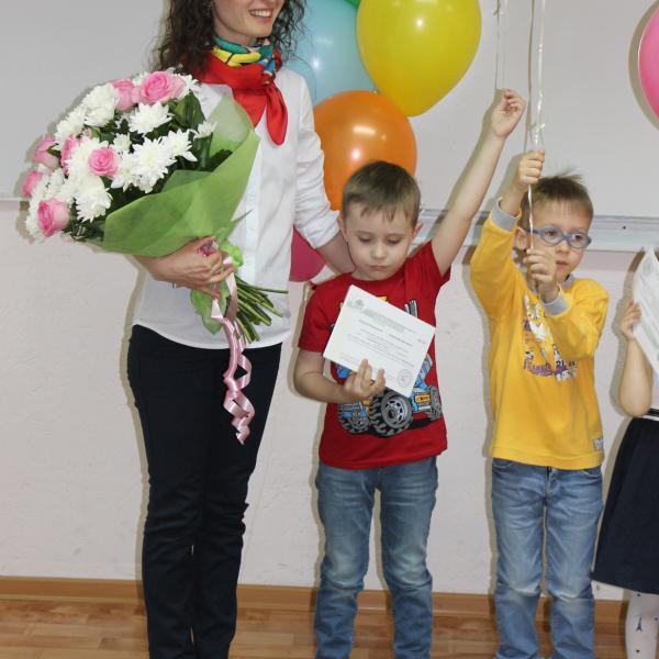 Сын удовлетворенно разглядывает заслуженный сертификат об окончании первого года обучения.